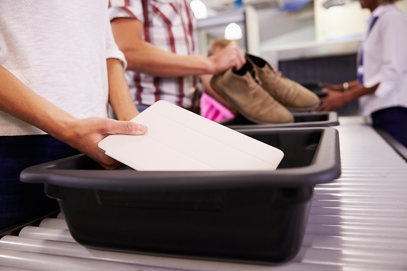 Man puts tablet into tray for airport security check