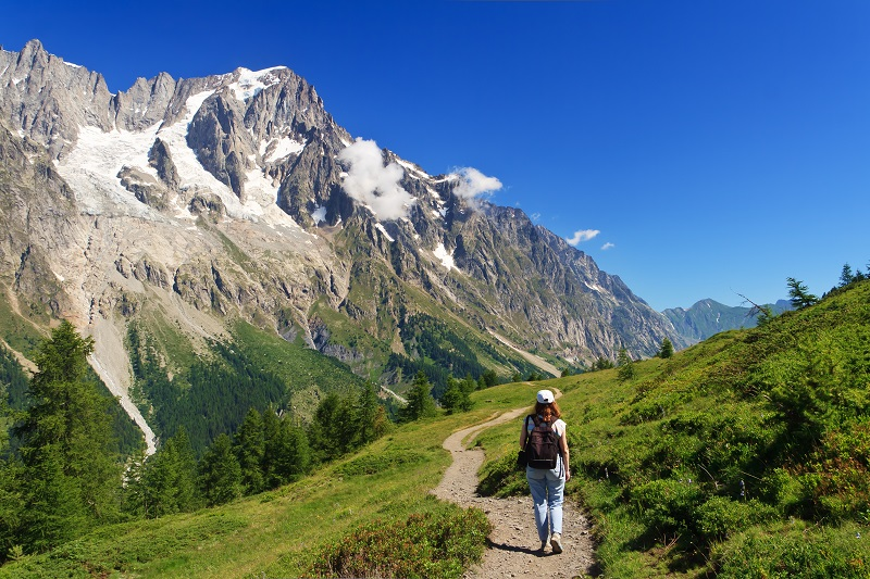 Hiker in Ferret Valley with Mont Blanc in background, Aosta Valley, Italy